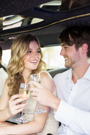 well dressed: Well dressed couple drinking champagne in a limousine on a night out