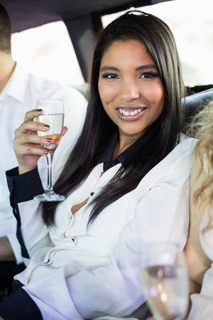 limousine: Well dressed woman drinking champagne in a limousine on a night out