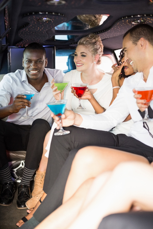 limousine: Well dressed people drinking cocktails in a limousine on a night out
