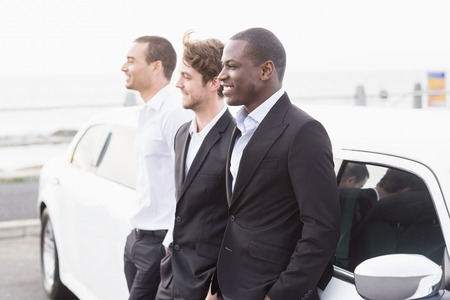 well dressed: Well dressed men posing leaning on a limousine on a night out Stock Photo
