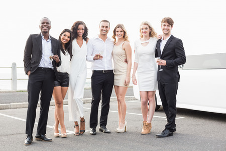 well dressed: Well dressed people posing next to a limousine on a night out