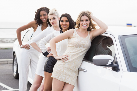 well dressed: Well dressed women posing leaning on a limousine on a night out
