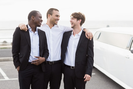 night out: Handsome men posing next to a limousine on a night out