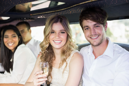well dressed: Well dressed people drinking champagne in a limousine on a night out