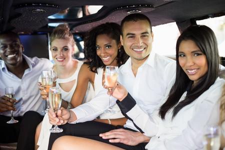 Dobře oblečení lidé pít šampaňské v limuzíně v noci ven Reklamní fotografie