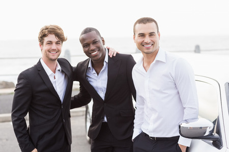 night out: Well dressed men posing next to a limousine on a night out Stock Photo