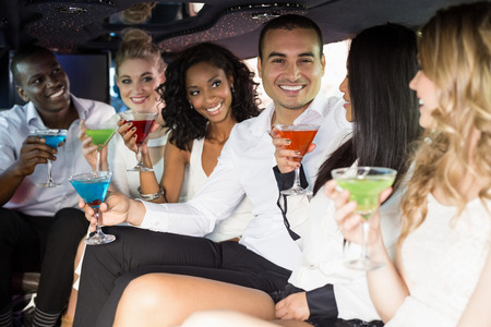 together with long tie: Well dressed people drinking cocktails in a limousine on a night out
