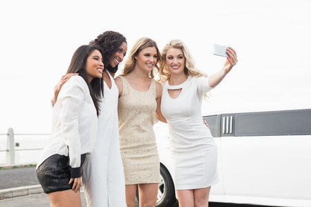 well dressed: Well dressed women taking a selfie next to a limousine on a night out Stock Photo