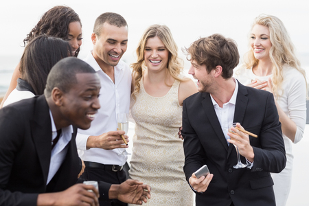 well dressed: Well dressed people looking smartphone on a night out Stock Photo