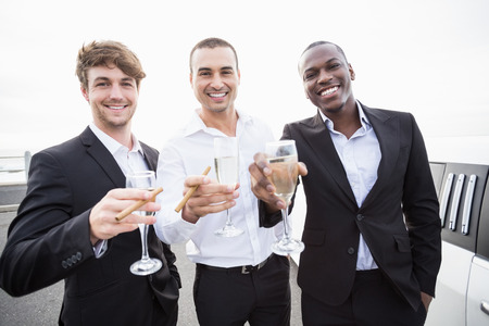night out: Well dressed men drinking champagne next to a limousine on a night out