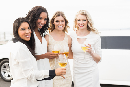 white party: Well dressed men drinking wine next to a limousine on a night out