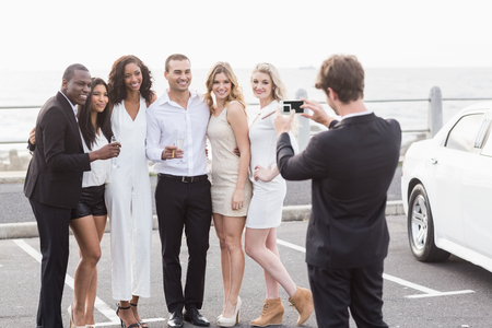 night out: Well dressed people taking pictures next to a limousine on a night out