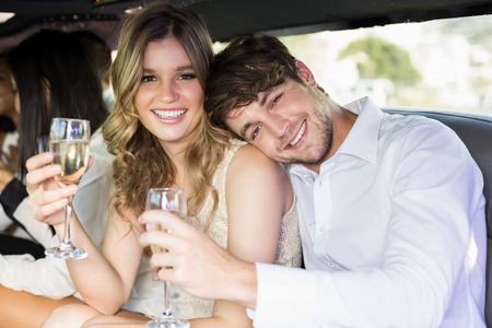 limousine: Well dressed couple drinking champagne in a limousine on a night out