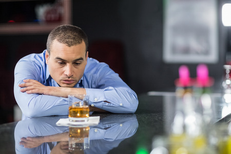 seclusion: Depressed businessman looking at whisky glasses in a pub Stock Photo