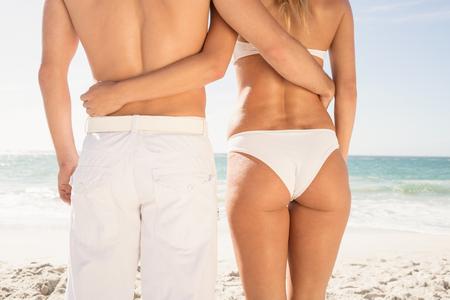 beachwear: Young couple in beachwear embracing on the beach