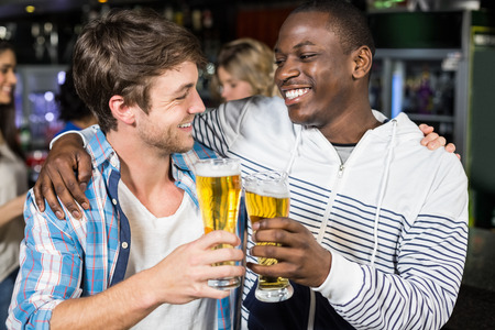 Smiling friends tasting with beer with their friends in a nightclub