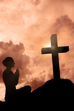 Content brunette in white sitting in lotus pose against cross religion symbol shape over sunset sky