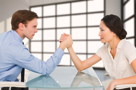 standoff: Business couple arm wrestling at desk against room with a lot of windows