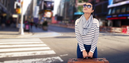 Asian woman with luggage looking up against blurry new york street Banco de Imagens
