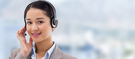 swivel chair: Portrait of a good looking operator posing with a headset against close up of swivel chair in an office