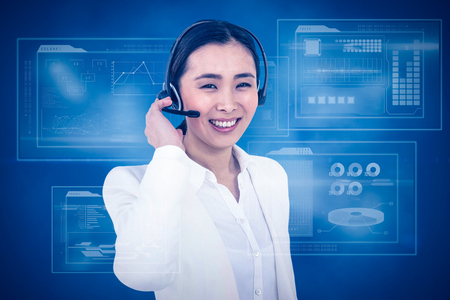 royal blue: Smiling businesswoman using headset against royal blue
