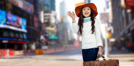 greet eyes: Asian woman with hat holding luggage  against blurry new york street Stock Photo