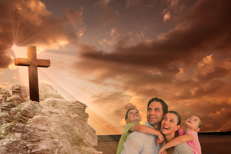family looking up: Happy young family looking up together against cross religion symbol shape over sunset sky Stock Photo