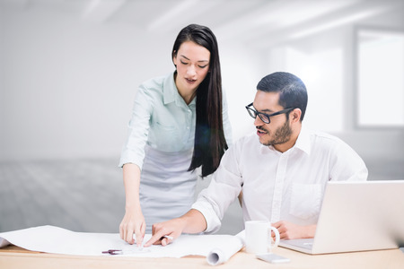 open floor plan: Casual architecture team working together at desk against white room with windows Stock Photo