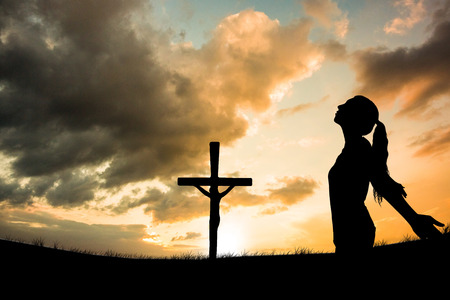 jesus standing: Side view of woman with arms outstretched and eyes closed  against cross religion symbol shape over sunset sky Stock Photo