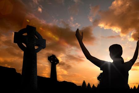 manos levantadas al cielo: La mujer en los casuals con las manos levantadas sobre fondo blanco contra cruz celta forma de s�mbolo de la religi�n sobre el cielo del atardecer