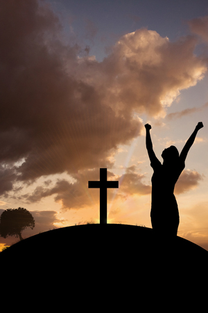 cross arms: Side view of woman with arms raised  against cross religion symbol shape over sunset sky