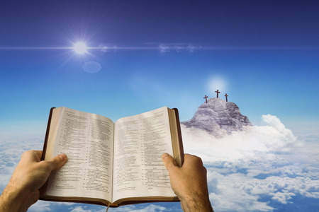 Man holding a holy bible against cross religion symbol shape in the sky
