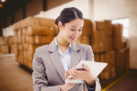 electronics industry: Portrait of a businesswoman using a tablet computer against cardboard boxes in warehouse