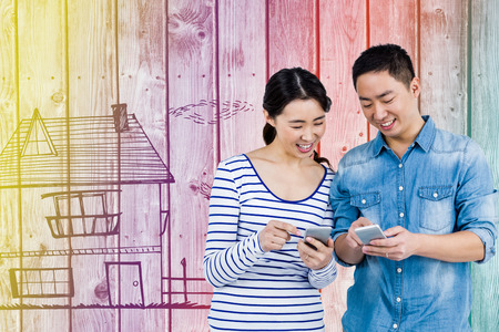 message board: Couple using smartphone against digitally generated grey wooden planks Stock Photo