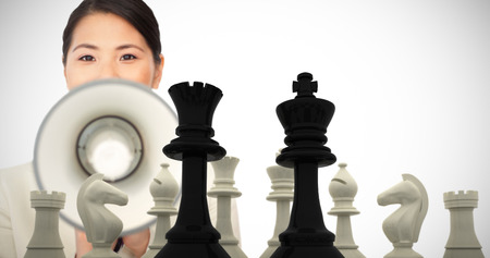 pawn adult: Young businesswoman shouting through a megaphone  against black king and queen standing in front of white pieces Stock Photo