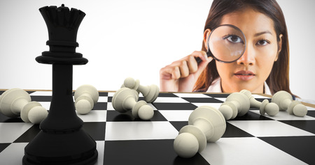 looking through: Businesswoman looking through magnifying glass against black queen standing with fallen white pawns