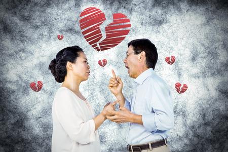 argument: Older asian couple having an argument against red heart