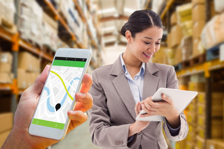 application icons: Hand holding smartphone against shelves with boxes in warehouse