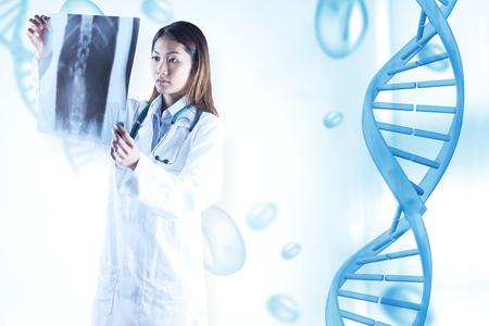 mri scan: Asian doctor checking MRI scan against blue chromosomes on blue background