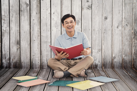 legs folded: Smiling man reading books against digitally generated grey wooden planks Stock Photo