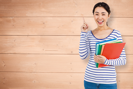 lady hand: Cheerful woman pointing up while holding files against overhead of wooden planks