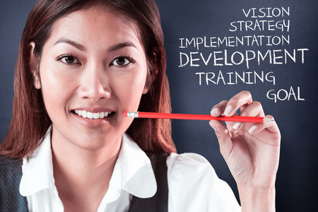 people development: Smiling businesswoman holding a pencil against navy blue