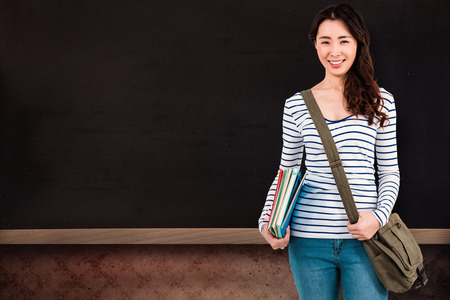 shoulder bag: Cheerful woman with shoulder bag and files against blackboard on wall