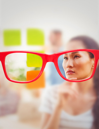 concentrated: Glasses against concentrated businesswoman looking post its on the wall