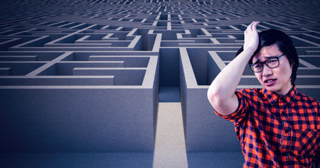 desolación: Sad hipster holding his head with his hand against entrance to difficult maze puzzle Foto de archivo