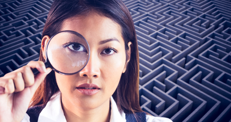 looking through: Businesswoman looking through magnifying glass against difficult maze puzzle Stock Photo