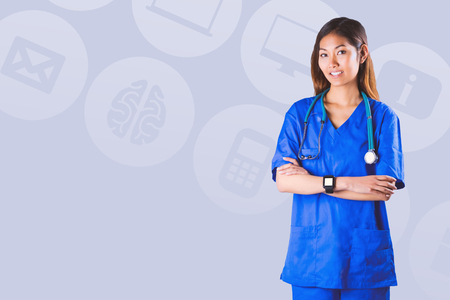 crossing arms: Asian nurse with stethoscope crossing arms against pastel blue Stock Photo