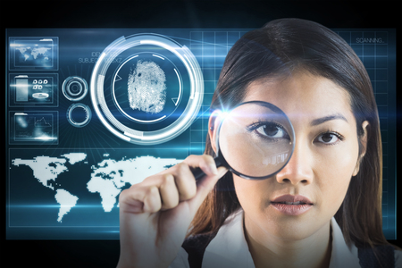 looking through: Businesswoman looking through magnifying glass against digital security hand print scan Stock Photo