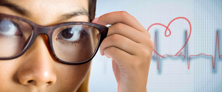holding close: Close up view of a businesswoman holding her eyeglasses against medical background with red ecg line Stock Photo