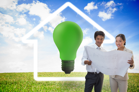 green light bulb: Estate agent looking at blueprint with potential buyer against green light bulb with white house outline